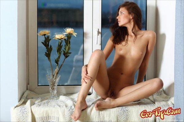 Молодая, голая милашка у окна.